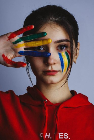 woman-in-red-hoodie-jacket-with-blue-yellow-and-green-paint-3660029